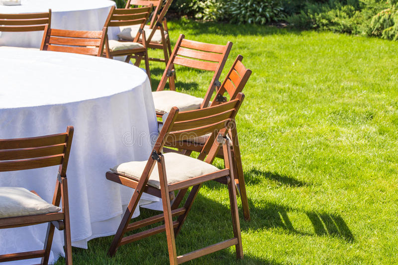 Round table covered with white cloth and chairs stand on a green lawn outdoors . royalty free stock image