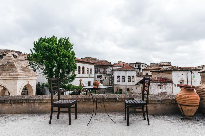 Round table and wooden chairs on terrace and historical houses behind. In cappadocia, turkey stock photo