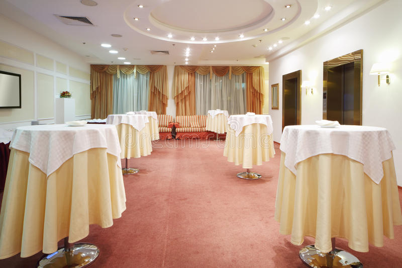 Round tables with white tablecloths and sofas in buffet stock photos