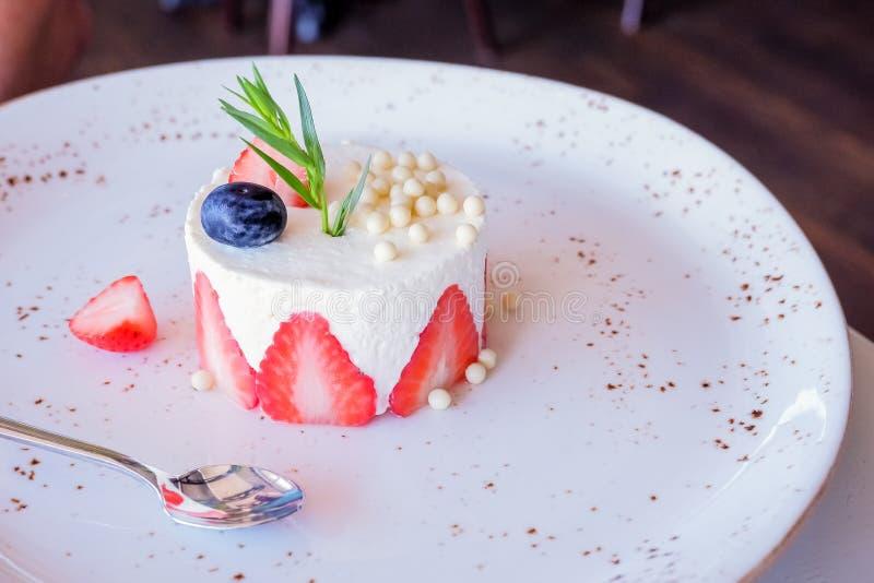 Round truskawkowi mini cheesecakes z solankowym karmelem i halfs truskawki upiększającymi z istnymi błękitnymi okwitnięciami, zdjęcia royalty free