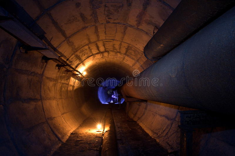 Round underground tunnel of heating duct with rusty tubes.  stock photos