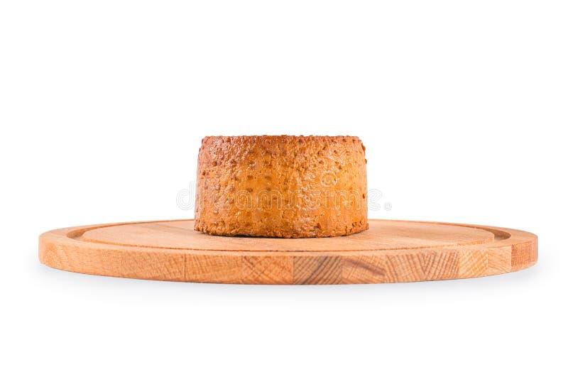 Round uwędzony ser na tnącej desce odizolowywającej z ścinkiem obraz royalty free