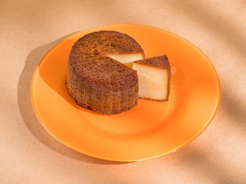 Round uwędzony ser z segmentu cięciem na koloru żółtego talerzu obraz royalty free