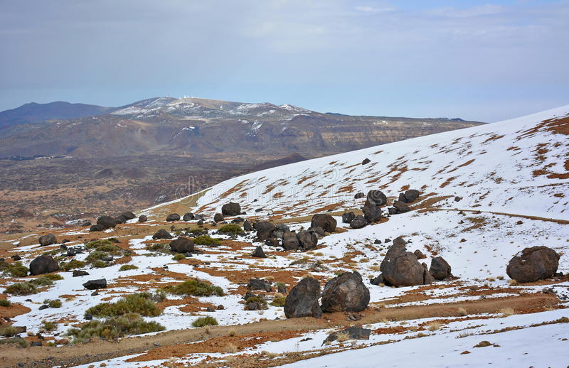 Round vulcano boulders on mountain snowy slope royalty free stock photography