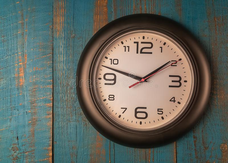 Round wall clock against old wooden blue table. stock image