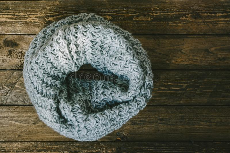 Round warm knitted scarf. Hand-knitted on wooden table royalty free stock image