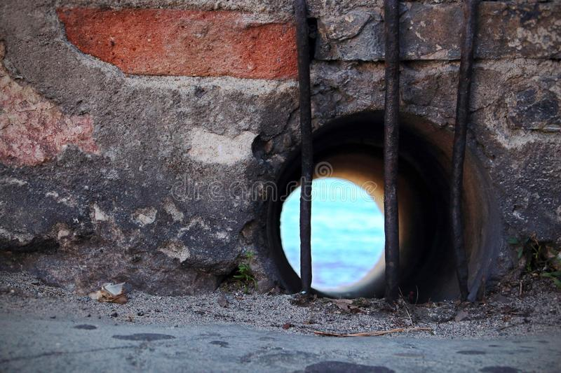 Round water drain window in red brick wall behind metal bars with view on blue sea water stock photos