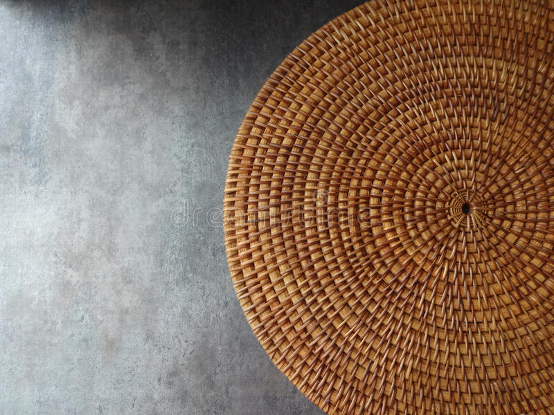 Round Weave Mat Background. A brown, braided, round, weave mat against a gray background royalty free stock images