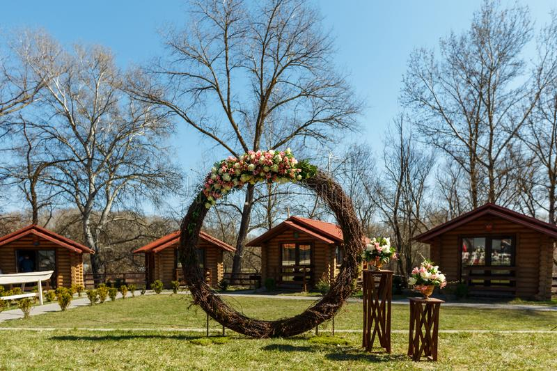 Round wedding arch from branches decorated with flowers and decor around it royalty free stock photos