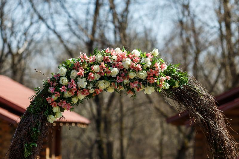 Round wedding arch from branches decorated with flowers and decor around it royalty free stock photography