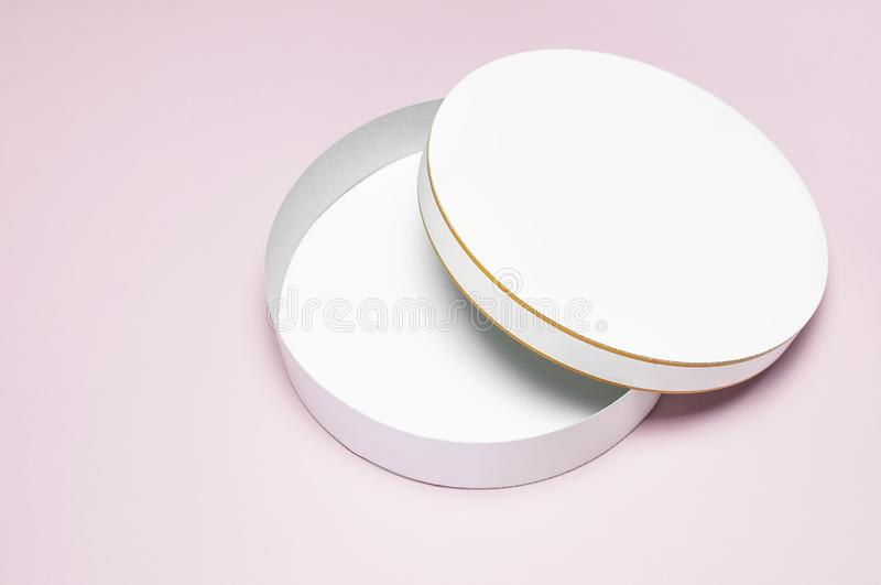 Round white cardboard blank box top view flat lay. Mock up on pink background. Packaging design, an empty box for shopping. stock photo