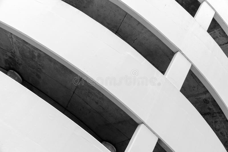 Round white concrete building exterior. Parking lot, round white concrete building exterior, abstract fragment royalty free stock photo