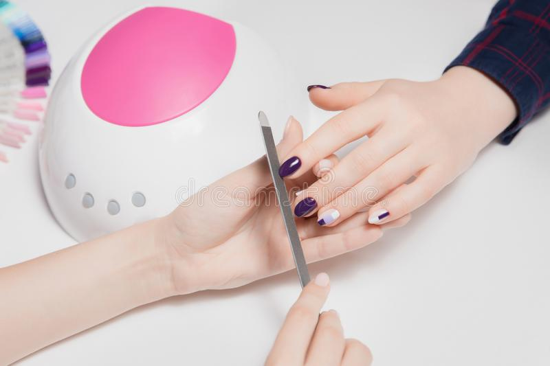 Round white and pink lamp for gel Polish. Beautiful woman`s hands do manicure in foreground. royalty free stock images