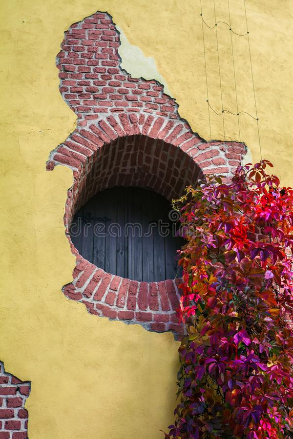 Round window - a loophole in a brick wall of the Tower Ruin in the Catherine Park and the curling garden ivy in bright autumn royalty free stock photo