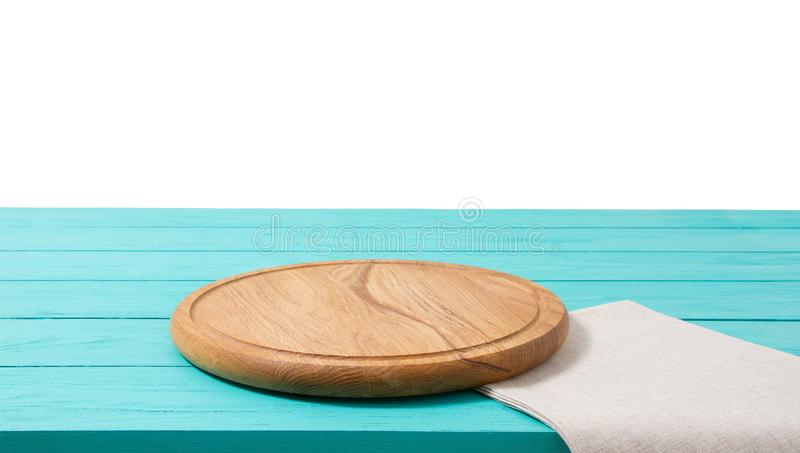 Round wood pizza cutting board and tablecloth on blue wooden table isolated on white background. Top view and copy space, Empty royalty free stock photos