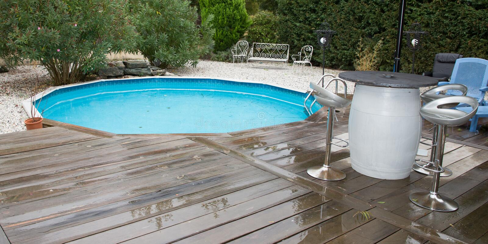 Small round swimming pool in home garden. Round wood pool for swimming in garden home stock photo