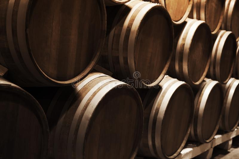 Round wooden barrels in dark winery. Wine production. Round wooden barrels in dark winery, close up photo with selective focus royalty free stock photos