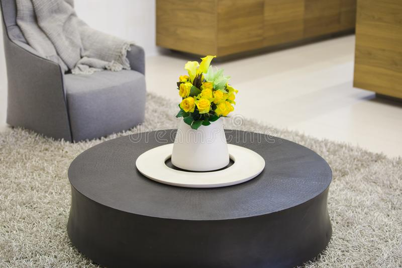 Round wooden coffee table in the living room with a vase of flowers in the center of the table, modern interior of the living room royalty free stock photo