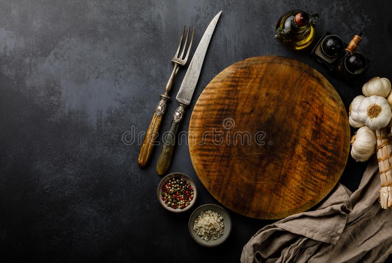 Round wooden Cutting board and Spices for cooking on dark concrete backdrop Surface copy space royalty free stock images
