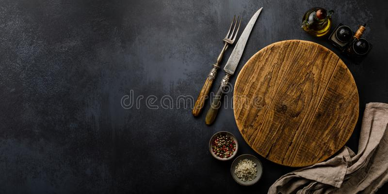 Round wooden Cutting board and Spices for cooking on dark concrete backdrop Surface copy space royalty free stock image