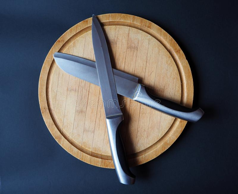 Round wooden cutting board with two knives royalty free stock photo