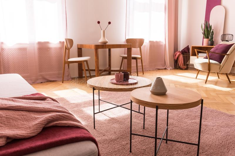 Tables on pink carpet in apartment interior with couch and armchair. Real photo. Round wooden tables on pink carpet in apartment interior with couch and armchair stock images