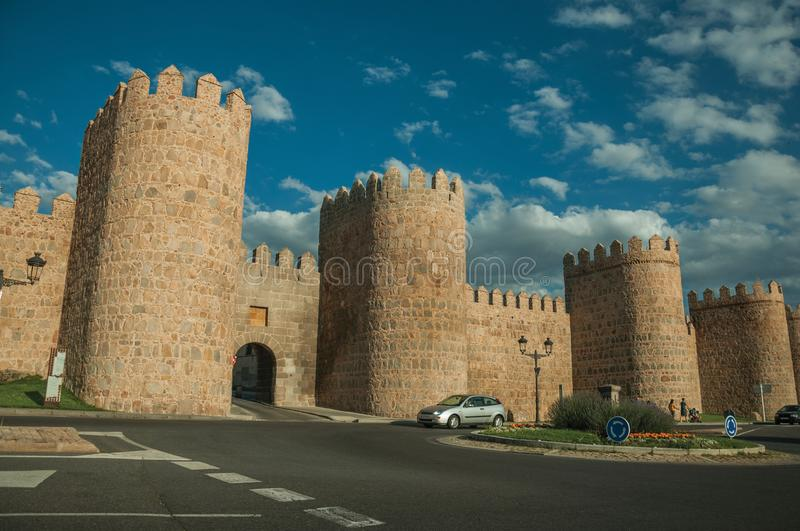 Roundabout in front gateway and large wall encircling Avila. Avila, Spain - July 22, 2018. Roundabout with cars in front gateway and towers in the wall around stock photography
