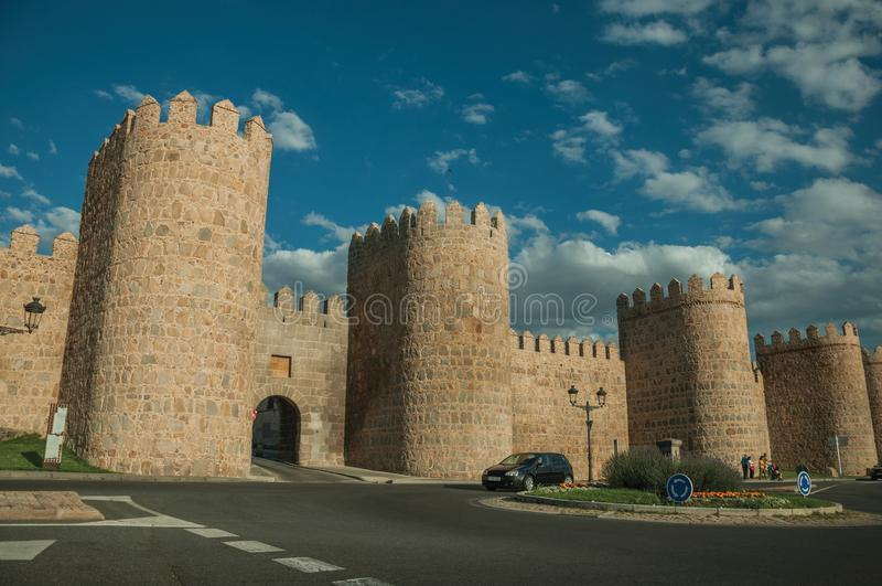 Roundabout in front gateway and large wall encircling Avila. Avila, Spain - July 22, 2018. Roundabout with cars in front gateway and towers in the wall around stock photo