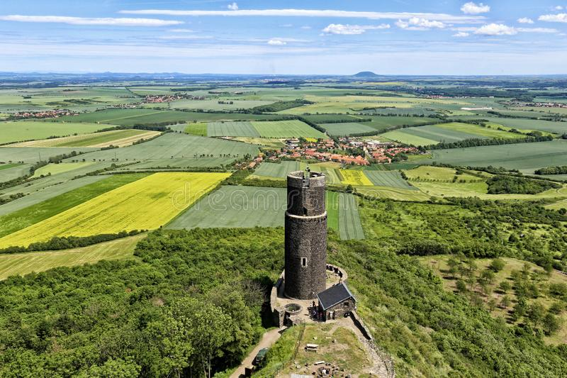 Rounded black tower of Hazmburk castle ruins with flat landscape below stock photography