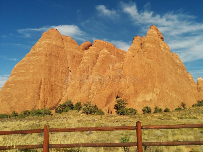 Rounded hills behind wooden fence at Arches National Park. With grass and bushes royalty free stock images