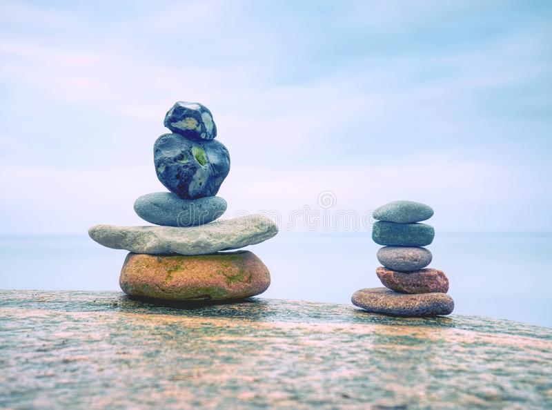 Rounded pebbles stack in peaceful evening with smooth ocean stock image