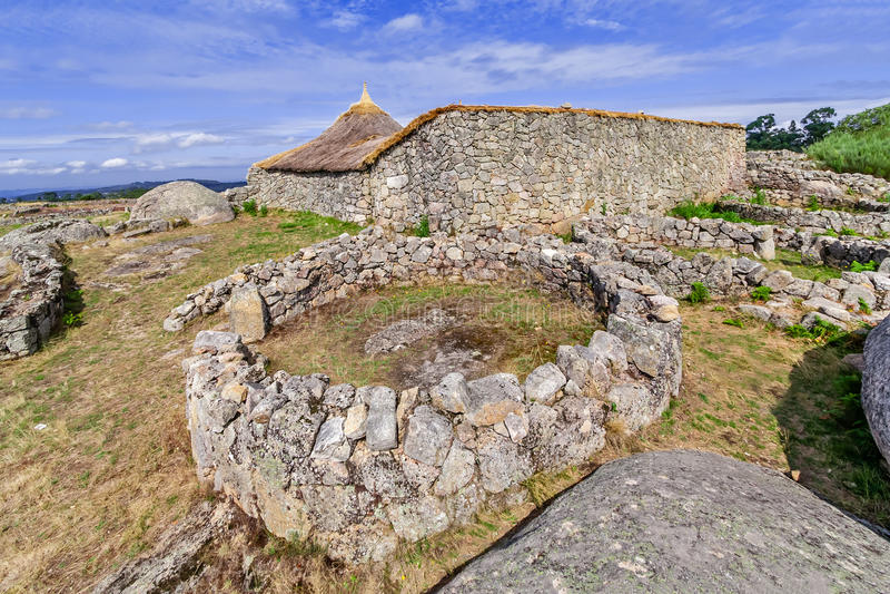 Roundhouseruïnes en het opnieuw opgebouwde gebouw van de familiekern in Citania DE Sanfins stock afbeelding