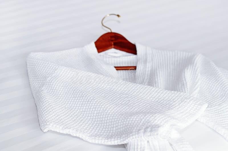 Roupão branco na cama imagens de stock