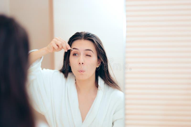 Roupão vestindo da mulher que arranca suas sobrancelhas após o chuveiro fotos de stock royalty free