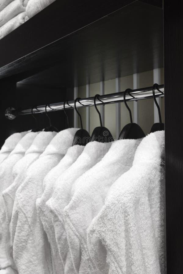 Roupões brancos, descansos, toalhas, pendurando no armário de madeira da sala do serviço no hotel fotografia de stock royalty free