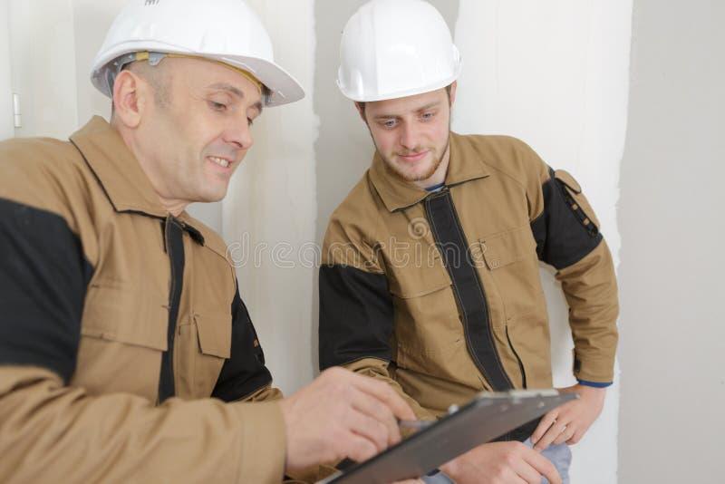 Roup uśmiechnięci budowniczowie z schowkiem i elektrycznym panelem indoors obraz royalty free