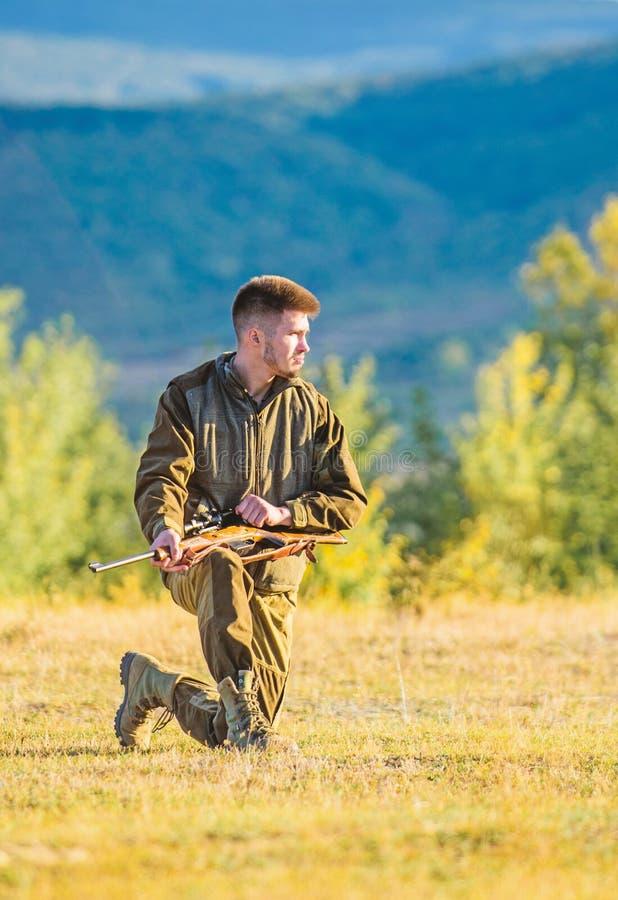 Roupa caqui do caçador pronta para caçar o fundo das montanhas da arma da posse Troféu do tiro da caça Caçador com procura do rif fotos de stock royalty free