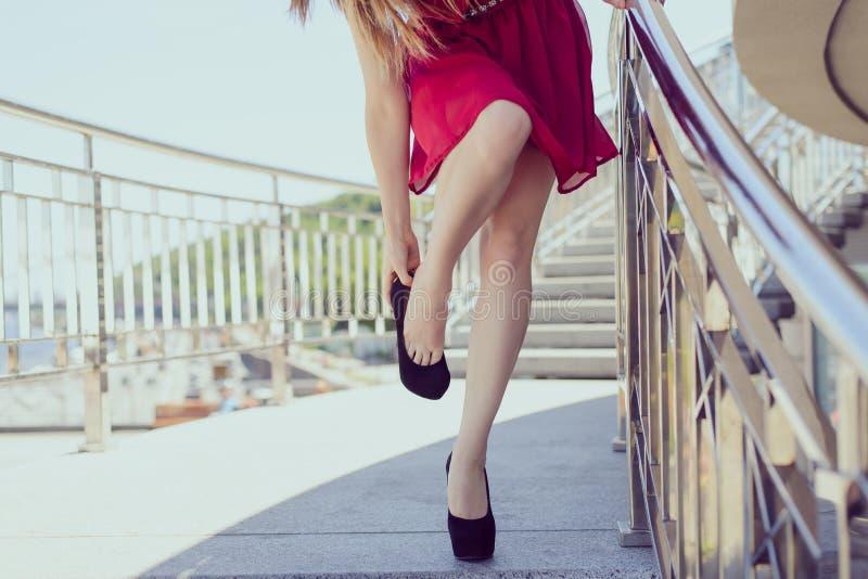 A roupa curto vermelha pequena demasiado grande despe o conceito elegante luxuoso Feche acima da foto da senhora cansado esgotada foto de stock