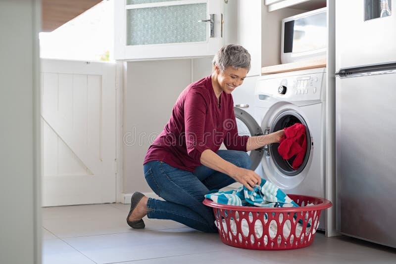 Roupa da carga da mulher na máquina de lavar imagens de stock royalty free