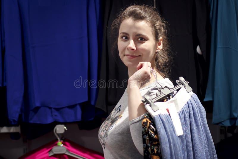 Roupa das compras da moça na loja elegante do boutique Conceito da compra A menina na loja de roupa está guardando coisas em ganc foto de stock royalty free