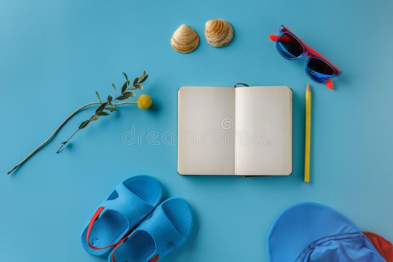 A roupa das crianças do verão e o caderno em um fundo azul brilhante, vista superior fotografia de stock