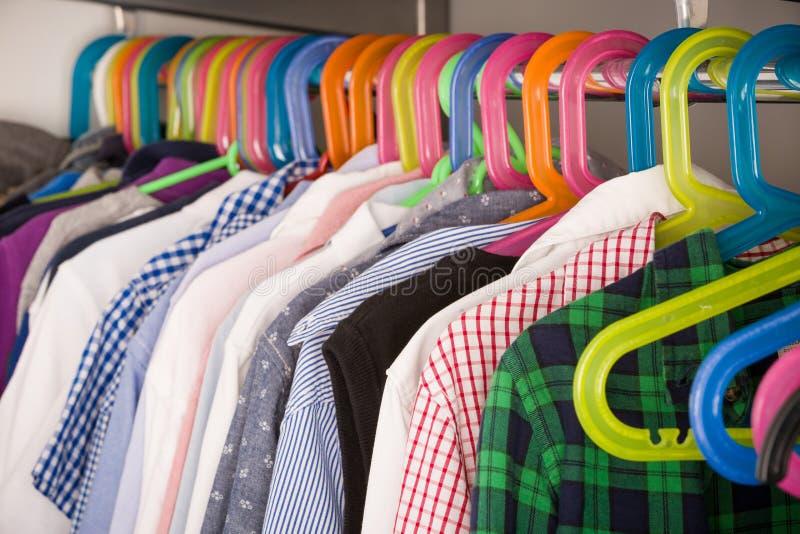 Roupa das crianças em ganchos em uma sala vestuário com roupa do menino em ganchos Conceito da compra e da consumi??o imagens de stock royalty free