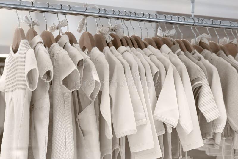A roupa das crianças fez de telas naturais pendura em ganchos imagens de stock