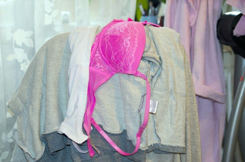 A roupa das mulheres que pendura em uma cadeira O sutiã cor-de-rosa das mulheres fetish foto de stock royalty free