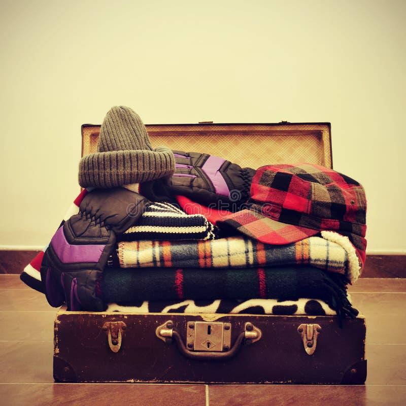 Roupa de aquecimento em uma mala de viagem imagens de stock royalty free