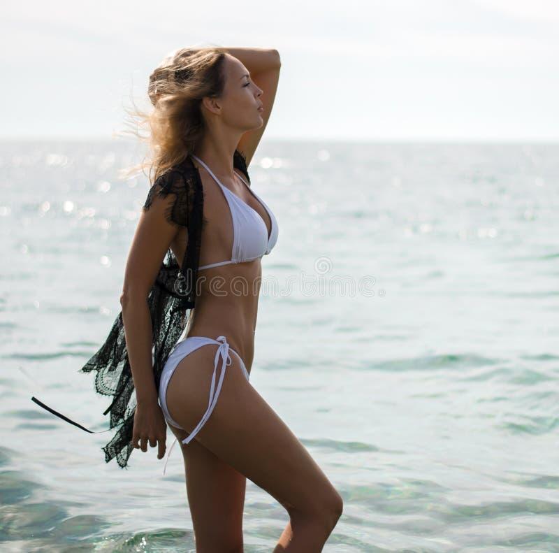 Roupa de banho branco vestindo da mulher loura bonita nova da forma e estada preta do cabo da praia do laço no mar fotografia de stock