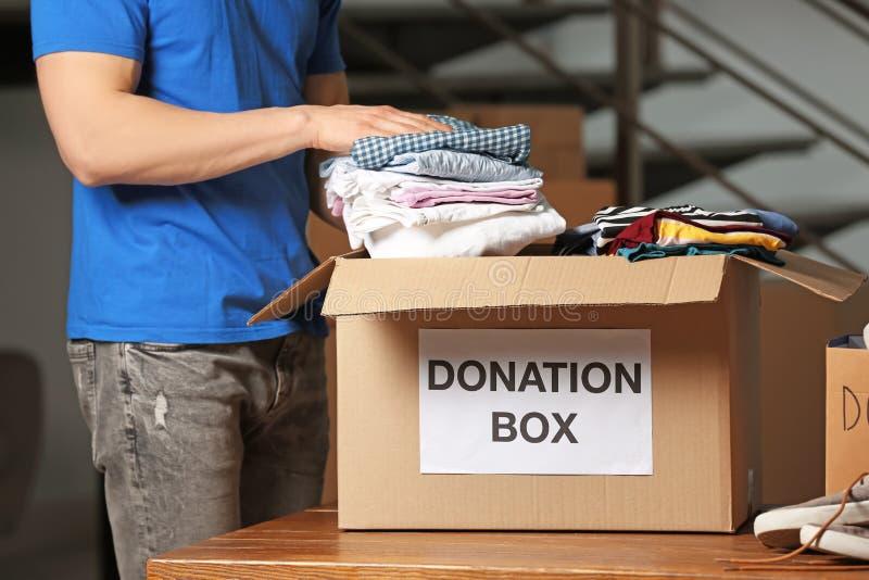 Roupa de colocação voluntária do homem na caixa da doação imagem de stock