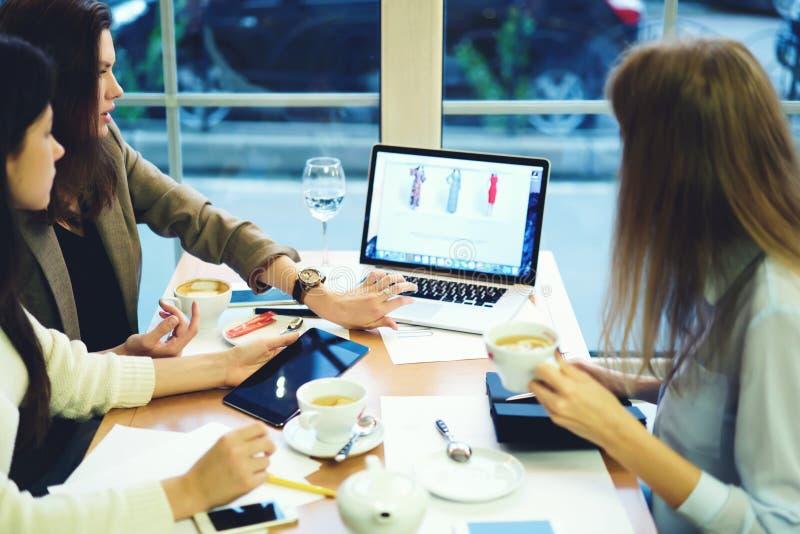 Roupa de desenhistas das meninas que trabalha junto a compra nas redes sociais que mostram produtos da empresa através do portáti fotografia de stock