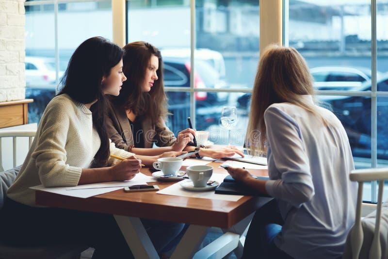 Roupa de desenhistas das meninas que trabalha junto ideias usando o laptop e o rádio 5G para fazer planeamentos e contabilidades imagem de stock