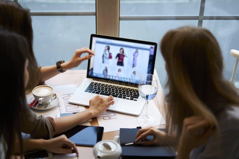 Roupa de desenhistas das meninas que trabalha junto o coffeebreak no café usando o laptop com zombaria acima da tela foto de stock royalty free